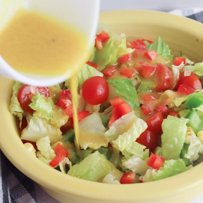 grilled corn on the cob salad in a bowl with lettuce, tomatoes and sweet pepper with a honey mustard dressing being poured over the top