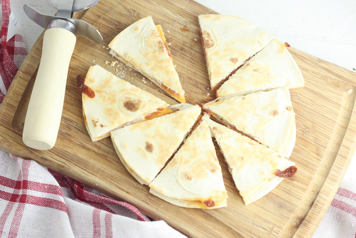 pepperoni and mozarella quesadilla cut into 8 slices on a wooden chopping board