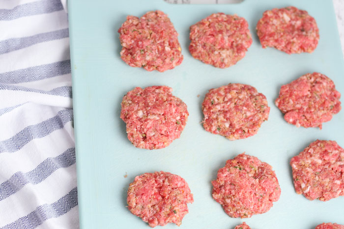 raw meatballs on a baking sheet ready to be stuffed with mozzarella cheese