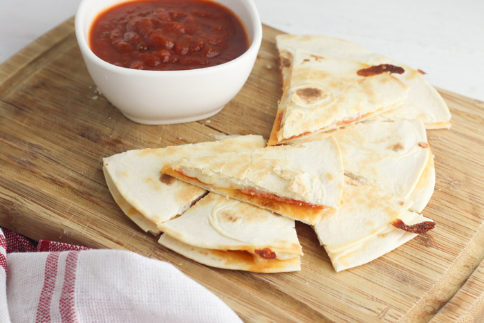 quesadillas on a wooden chopping board with a white bowl of tomato dipping sauce