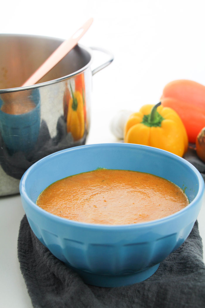 roasted red pepper soup in a blue bowl next to a range of sweet peppers and a pan for cooking