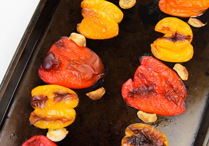 roasted peppers and garlic on a baking tray ready for soup